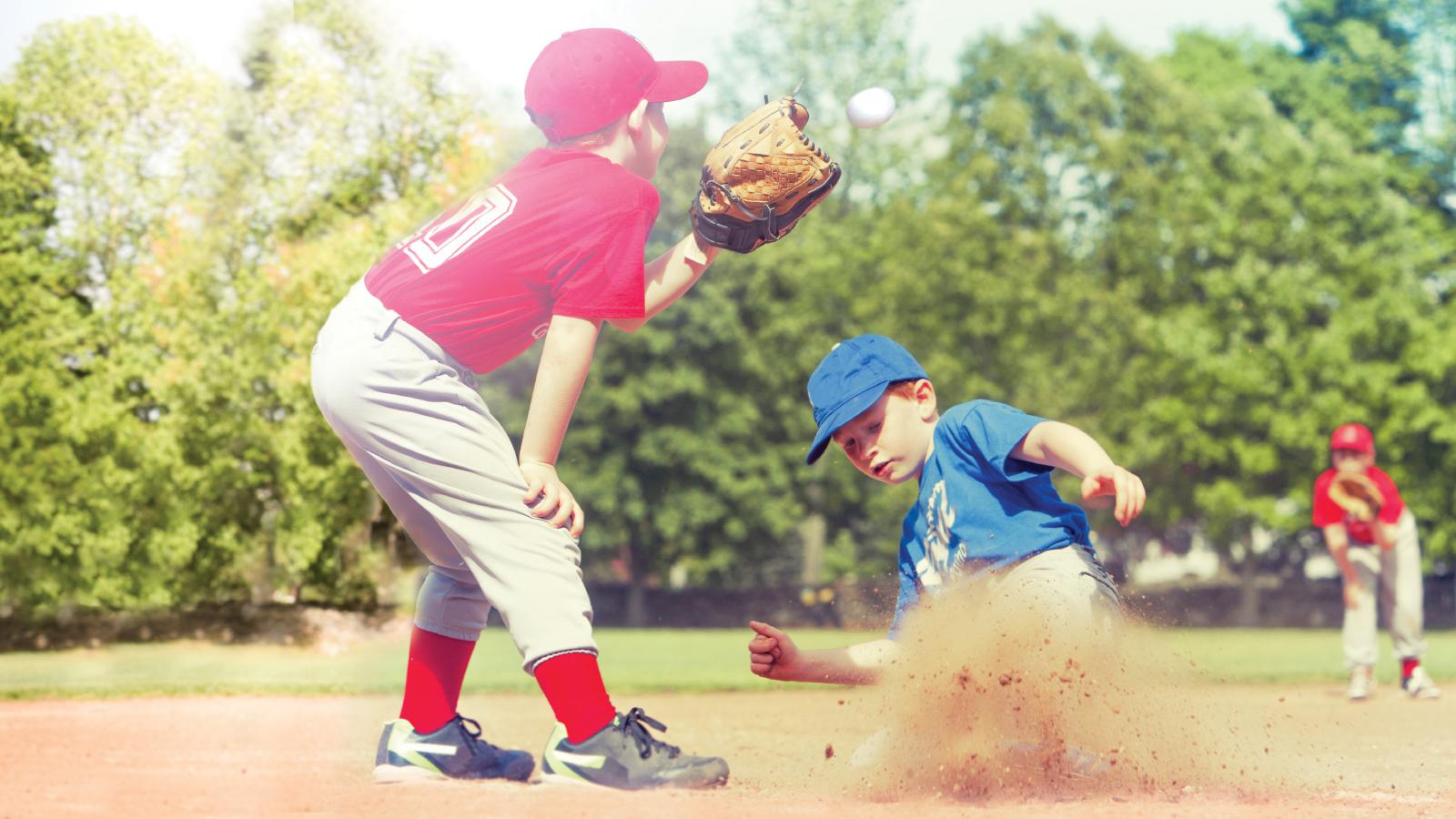Kids playing baseball sliding into home plate